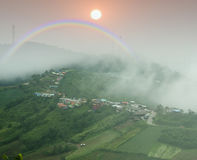 Regenboog op nevelige berg in het regenachtige seizoen Stock Foto