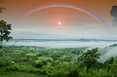Regenboog op nevelige berg in het regenachtige seizoen Stock Afbeelding