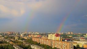 Regenboog over de daken van Omsk Stock Foto's