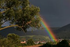 Regenboog over dorp stock fotografie