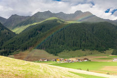 Regenboog over een klein dorp in de Dolomietbergen, Italië Royalty-vrije Stock Afbeeldingen