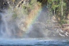 Regenboog over een krachtige stroom van water onder de waterval van de rivier Urich in Oostelijke Sayan Royalty-vrije Stock Afbeeldingen