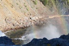 Regenboog over een krachtige stroom van water onder de waterval van de rivier Urich in Oostelijke Sayan Stock Foto