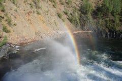 Regenboog over een krachtige stroom van water onder de waterval van de rivier Urich in Oostelijke Sayan Stock Fotografie