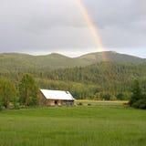 Regenboog over een schuur. Stock Afbeeldingen