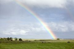 Regenboog over groen weiland Stock Afbeeldingen