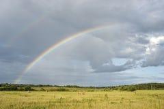 Regenboog over het gebied stock afbeelding