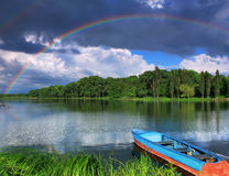 Regenboog over het meer met een boot Stock Afbeelding