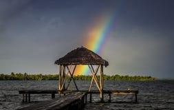Regenboog over houten pijler Stock Foto