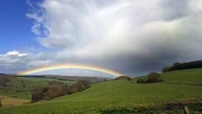 Regenboog over landschap met donkere wolken stock afbeeldingen