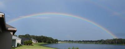 Regenboog over meer stock foto