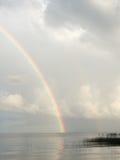 Regenboog over Meer met Wolken Stock Foto's