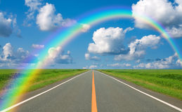 Regenboog over rechte weg Stock Afbeeldingen