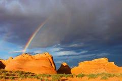 Regenboog over rode rotsen Stock Afbeeldingen