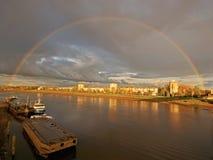 Regenboog over stad en rivier Stock Afbeeldingen