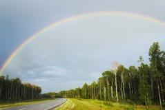 Regenboog over weg Stock Foto's