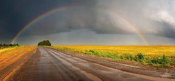 Regenboog over weg Stock Afbeeldingen