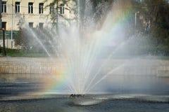 Regenboog in plonsen van een fontein als abstracte achtergrond stock foto