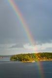 Regenboog in regen tijdens zonneschijn in overzees Royalty-vrije Stock Afbeeldingen