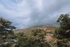 Regenboog tegen de hemel en bergen met een pijnboombos stock foto's