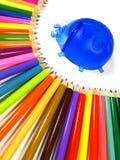Regenboog van kleurenpotloden en tribuneonzelieveheersbeestje Stock Foto