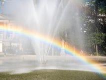 Regenboog van kunstmatige fontein in park Stock Afbeeldingen