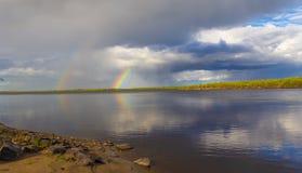 Regenboogdubbel over de rivier stock fotografie