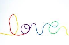 Regenboogliefde het van letters voorzien met garen Stock Afbeeldingen