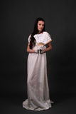 Regency. Female model with dark hair in a historical regency period empire waist dress holding a partially open hand fan Royalty Free Stock Image