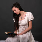 Regency. Female model posing in a historical regency period empire waist dress reading a book Royalty Free Stock Images