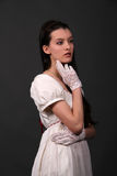 Regency. Female model in historical regency period empire waist dress and whit gloves in a thoughtful pose Stock Photos