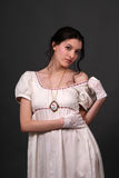 Regency. Female model with dark hair in historical regency period empire waist dress uncovering her shoulder Royalty Free Stock Photo