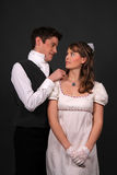 Regency. Couple in historical regency period costumes with the man putting on a necklace around her neck Stock Photos