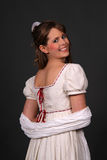 Regency. Female model in a historical regency period empire waist dress with a white shawl around her arms and smiling Stock Photo