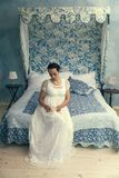 Regency lady sitting on canopy bed stock images