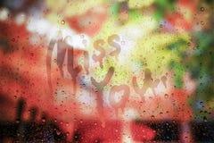 Regendaling op glas met juffrouw u tekst op glas, vage achtergrond die, liefdeconcept wordt geschreven, u missen concept dat stock fotografie