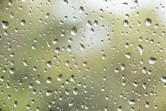Regendalingen bij een venster, met groene achtergrond stock fotografie