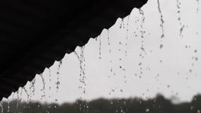 Regendalingen neer van een dak stock videobeelden