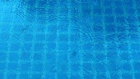 Regendalingen op blauw water zwembad Royalty-vrije Stock Foto's