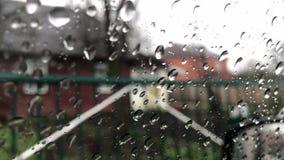 Regendalingen op de oppervlakte van vensterglazen met bewolkte achtergrond Natuurlijk Patroon van regendruppels Het drijven in re stock footage