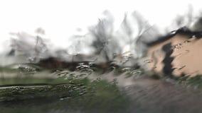 Regendalingen op de oppervlakte van vensterglazen met bewolkte achtergrond Natuurlijk Patroon van regendruppels Het drijven in re stock videobeelden