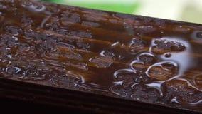 Regendalingen op een houten venstervensterbank zoals vloeibaar metaal of kwik stock video
