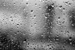 Regendalingen op een venster De dalingen van het water op vensterglas Achtergrond Stock Afbeelding