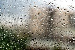 Regendalingen op een venster De dalingen van het water op vensterglas Achtergrond Stock Fotografie