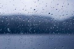 Regendalingen op een venster of waterdalingen op glasachtergrond stock afbeeldingen