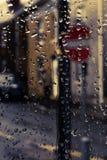 Regendalingen op het venster met straat erachter teken stock afbeelding