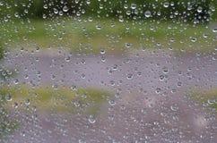 Regendalingen op het vensterglas tegen de achtergrond van groene aard in de zomer royalty-vrije stock foto's