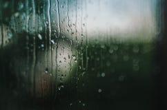 Regendruppels die een venster reduceren Stock Foto