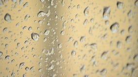 Regendruppels die neer binnen glasvenster glijden terwijl het regenen stock footage