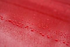 Regendruppels op ceramische met een laag bedekte rode auto met hydrophobic effect stock foto's